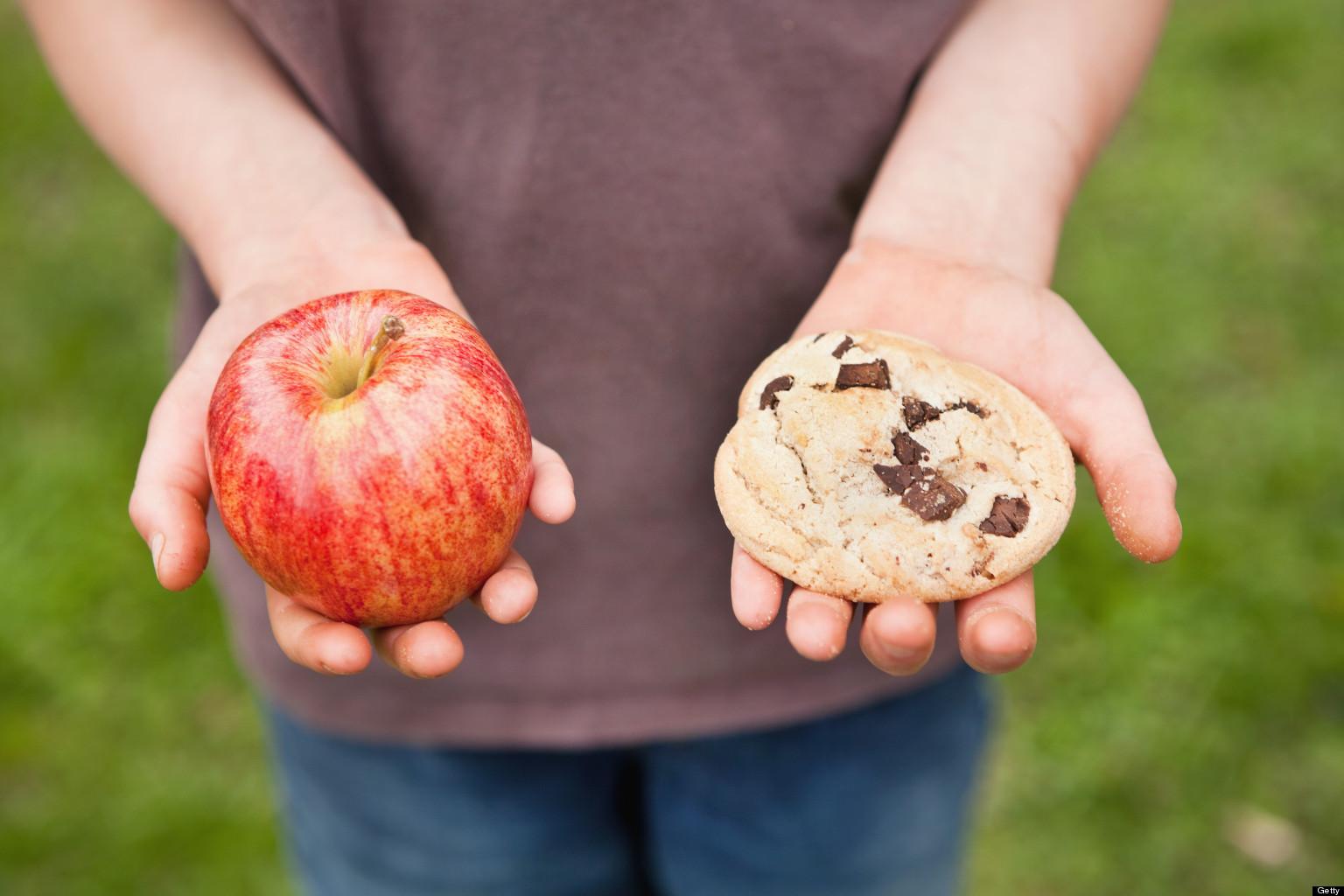 Menino segurando uma maça e um biscoito nas duas mãos.