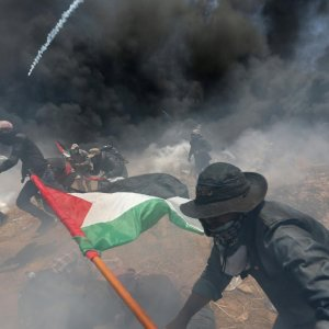 Palestinian demonstrators run for cover from Israeli fire and tear gas on May 14.