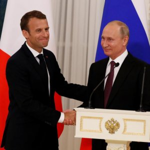 President Vladimir Putin (R) and his French counterpart Emmanuel Macron shake hands as they leave after a news conference in St. Petersburg on May 24.