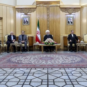 President Hassan Rouhani (C) talks to reporters in Tehran on Friday before flying to China.