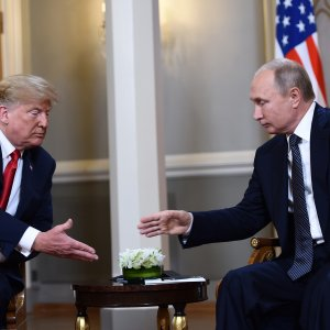 Russian President Vladimir Putin (R) and US President Donald Trump reach to shake hands before a meeting in Helsinki, on July 16.