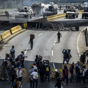 Opposition activists and riot police clash during a protest against President Nicolas Maduro in Caracas.