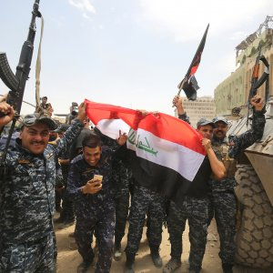 Members of the Iraqi federal police wave their country's national flag in celebration in the Old City of Mosul.