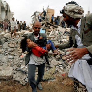 A man carries a five-year-old child rescued from the site of a Saudi-led airstrike that killed eight of her  family members in Sanaa, Yemen, August 25.