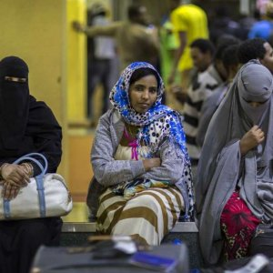Ethiopian women sit on a luggage conveyor belt as they wait for family members after being deported from Saudi Arabia, at the airport in Addis Ababa, Ethiopia, on Dec. 22.