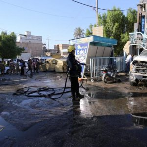 A firefighter hoses down a street after a suicide attack in Karbala