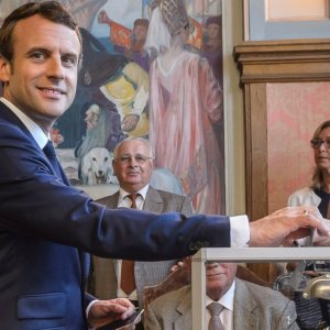 French President Emmanuel Macron (L) casts his ballot in the first round of the two-stage legislative elections, in Le Touquet, northern France, on June 11.