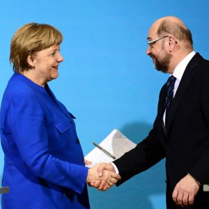 Angela Merkel (L) shakes hands with SPD leader Martin Schulz.