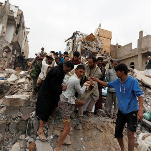 People carry the body of a woman they recovered from under the rubble of a house destroyed by a Saudi-led airstrike in Sanaa, Yemen on August 25.