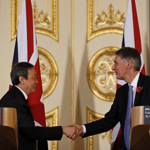 Ma Kai (L) and Philip Hammond shake hands after the press conference in Beijing, Dec. 16.