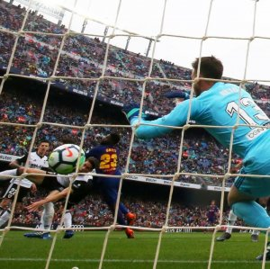 Barcelona's Samuel Umtiti scores his side's second goal past Valencia's Neto.