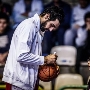 Arsalan kazemi signing a ball for a young fan