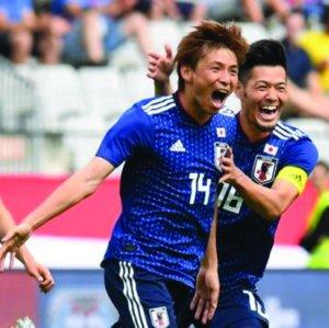 Japan players celebrate a goal.