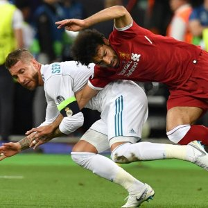 Mohamed Salah (R) goes down after a challenge from Real Madrid's Sergio Ramos.