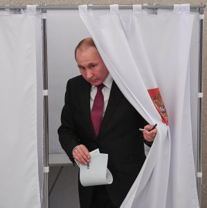 Presidential candidate, President Vladimir Putin, walks out of a voting booth at a polling station during Russia's presidential election in Moscow on March 18. (Photo: AFP)