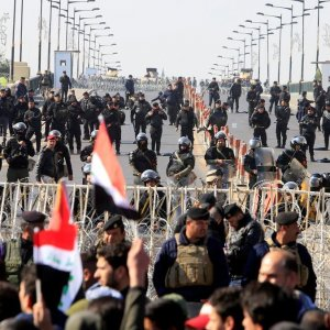Riot police stand in front of demonstrators during the protest near Baghdad's Green Zone on Feb. 11.
