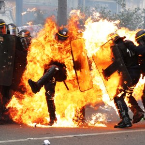 One riot police officer engulfed in flames in Paris, France, on May 1.