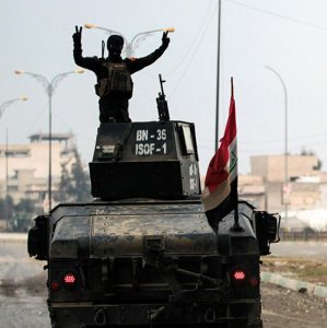 An Iraqi soldier rides an armored vehicle in Mosul.