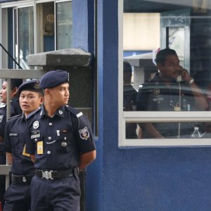 Police officers guard the main gate of the forensic department at Kuala Lumpur Hospital in Kuala Lumpur, Malaysia, on Feb. 22.