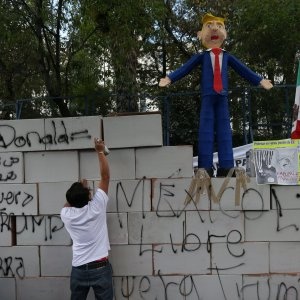 An effigy of Donald Trump stands on a symbolic wall built by protesters outside the US embassy in Mexico City.