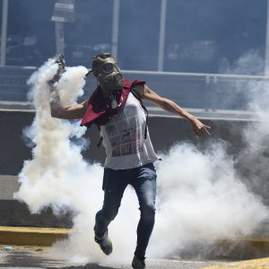 A demonstrator returns a tear gas during clashes with riot police in eastern Caracas on April 8.