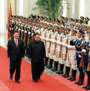 Kim Jong-un (R) inspecting an honor guard while accompanied by Chinese President Xi Jinping during a welcoming ceremony at the Great Hall of the People in Beijing on June 19.