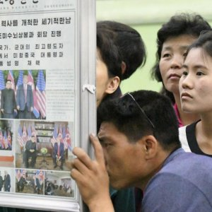 North Koreans watch the displayed local newspapers reporting the summit between the US and North Korea  at a subway station in Pyongyang on June 13.