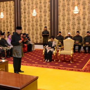 Mahathir Mohamad (standing L), wearing traditional Malay dress, took the oath of office on May 10.