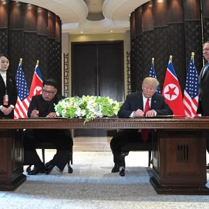 US President Donald Trump and North Korea's leader Kim Jong-un sign documents as US Secretary of State Mike Pompeo (R) and the North Korean leader's sister Kim Yo Jong (L) look on at a signing ceremony during the US-North Korea summit, at the Capella Hotel on Sentosa island in Singapore on June 12.