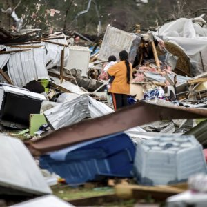 A woman holds a child while walking through a farm that was damaged  by a tornado on Jan. 22.