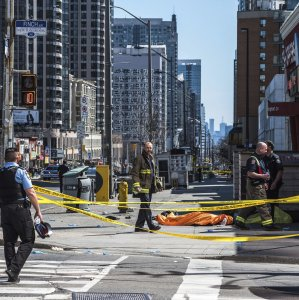 A body lies covered on the sidewalk in Toronto after a van mounted a sidewalk crashing into a number of pedestrians on April 23.