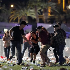 People carry a peson at the Route 91 Harvest country music festival after gun fire in Las Vegas, Nevada. (Photo: AFP)