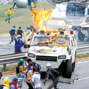 Demonstrators clash with a riot police armored car during a rally against President Nicolas Maduro in Caracas, Venezuela.