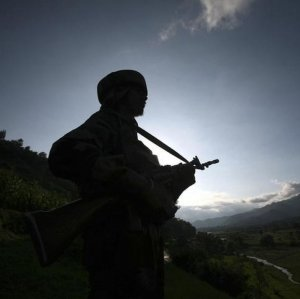 An Indian Army soldier stands guard while patrolling near the Line of Control, a ceasefire line dividing Kashmir between India and Pakistan in Poonch.