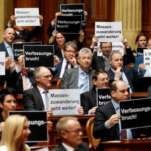 "Members of the conservative right Swiss People's Party held up signs that read ""breach of the constitution"" and ""mass immigration continues""."