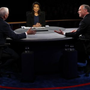 Tim Kaine (R) and Mike Pence discuss, as moderator Elaine Quijano looks on, October 4.