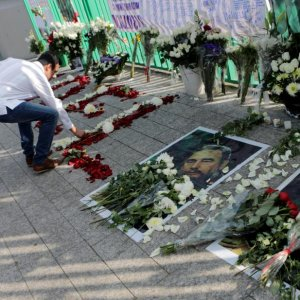 A supporter places flowers beside pictures of Fidel Castro as he attends a tribute ceremony, following the announcement of the death of Cuban revolutionary leader Castro outside the Cuban Embassy, in Mexico City, Mexico, on Nov. 27.