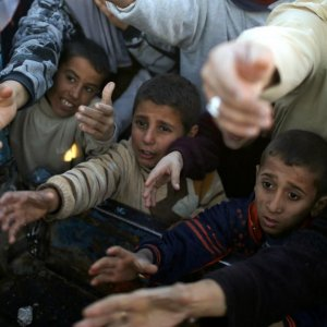 Displaced Iraqi boys ask for food at a food distribution point in Khazer camp, Iraq, on Nov. 21.