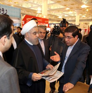 Ali Reza Bakhtiari, publisher and managing director of Financial Tribune and Donya-e-Eqtesad briefs President Hassan Rouhani at the fair in Tehran on Nov. 15.