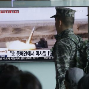 South Korean soldiers pass by a TV news program  showing a file footage of a missile launch conducted  by North Korea. (File Photo)