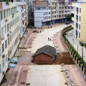 """Despite the surge in property sales, overall housing inventory remains a major issue across China. A """"nail house"""", the last building  in the area, sits in the middle of a road under construction in Nanning, Guangxi Zhuang Autonomous Region."""