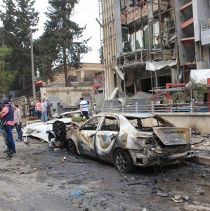 Journalists and civilians stand near the damage after rockets fired by insurgents hit the al-Dabit maternity clinic in  government-held parts of Aleppo city, Syria. (File Photo)