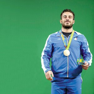 Iran's gold medallist Kianoush Rostami poses on the podium after the men's weightlifting 85 kg event during the Rio 2016 Olympics Games on August 12.