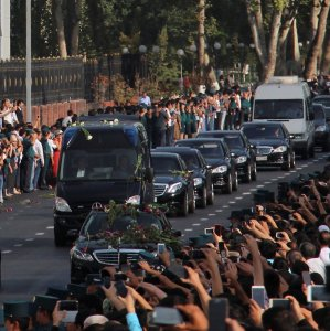 People pay tribute to the late Uzbek president, Islam Karimov, as the funeral motorcade passes along a road in Tashkent on Sept. 3.