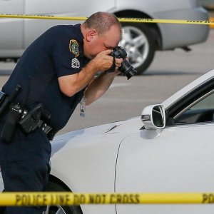 A police investigator photographs a vehicle with gunshot damage in Houston, Texas, USA, on Sept. 26.