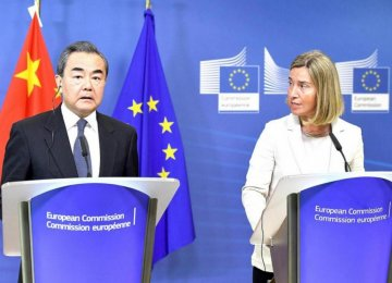 China's Foreign Minister Wang Yi (L) and EU foreign policy chief Federica Mogherini address a press conference at the European Commission in Brussels on Friday.