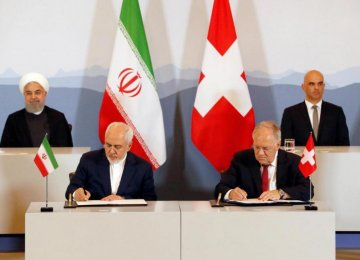 President Hassan Rouhani (top- L) and President Alain Berset (top-R) watch as Foreign Minister Mohammad Javad Zarif (L) and Swiss Economic Minister Johann Schneider-Ammann sign an agreement in Bern on July 3.
