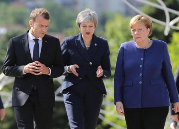 French President Emmanuel Macron (L), British Prime Minister Theresa May (C) and German Chancellor Angela Merkel walk during the EU-Western Balkans Summit in Sofia, Bulgaria on Thursday.