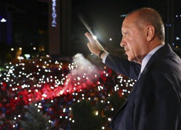 Turkish President Recep Tayyip Erdogan greets supporters gathered in front of the AKP headquarters  in Ankara, on June 25.