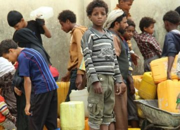 Displaced children in Yemen wait together and collect water.